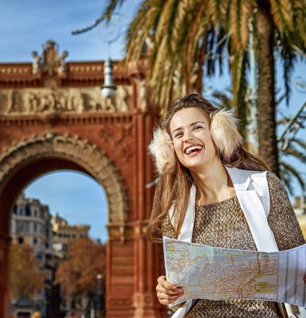 in Barcelona for a perfect winter. smiling modern fashion-monger in earmuffs near Arc de Triomf in Barcelona, Spain with map looking into the distance