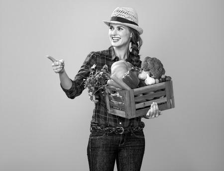 あなたのテーブルに健康的な食べ物。何かを指し示す新鮮な野菜の箱と黄色に隔離されたチェッカーシャツで笑顔の若い女性の栽培者の肖像画