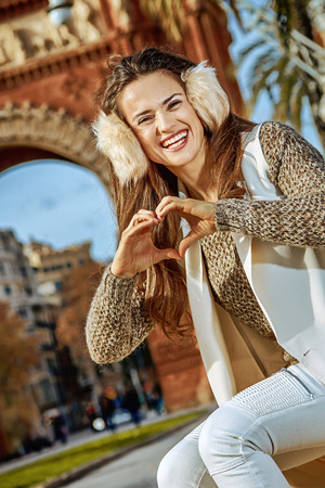 in Barcelona for a perfect winter. happy modern fashion-monger in earmuffs in Barcelona, Spain showing heart shaped hands Stock Photo