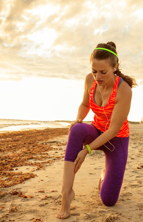 Refreshing wild sea side workout. healthy active woman in sport clothes on the seashore having leg injury