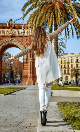in Barcelona for a perfect winter. Seen from behind cheerful young fashion-monger in earmuffs in Barcelona, Spain walking on a parapet