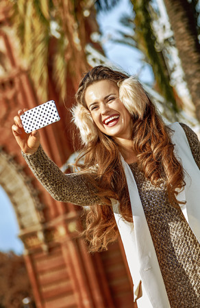 in Barcelona for a perfect winter. smiling elegant fashion-monger in earmuffs near Arc de Triomf in Barcelona, Spain with cellphone taking selfie