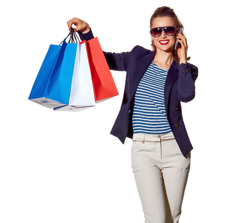 Luxury Shopping. The French way. Full length portrait of smiling young woman in sunglasses talking on a smartphone and showing shopping bags isolated on white