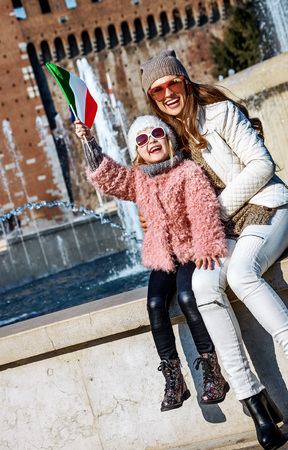 Rediscovering things everybody love in Milan. happy modern mother and daughter tourists in sunglasses in Milan, Italy rising flag Banco de Imagens