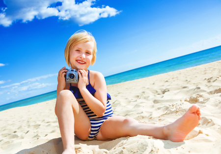 Sun kissed beauty. happy healthy girl in swimwear on the seacoast with retro photo camera 스톡 콘텐츠