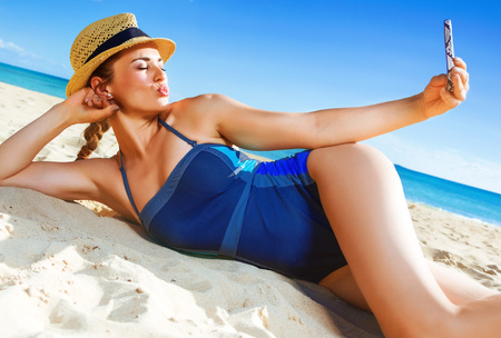Sun kissed beauty. healthy woman in swimsuit on the beach with smartphone taking selfie Stock Photo
