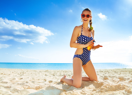 Sun kissed beauty. smiling young woman in swimsuit on the seashore with SPF Stock Photo
