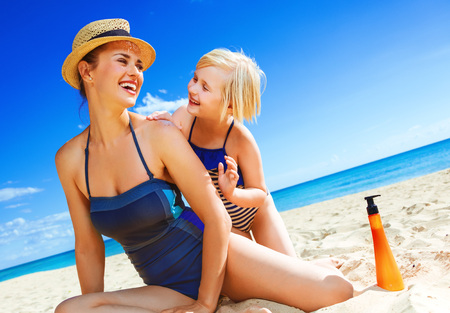 Sun kissed beauty. smiling young mother and child in beachwear on the seashore applying SPF