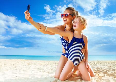 Sol beijou beleza. sorrindo, saudável, mãe filha, em, beachwear, ligado, a, seacoast, com, câmera digital, levando, selfie