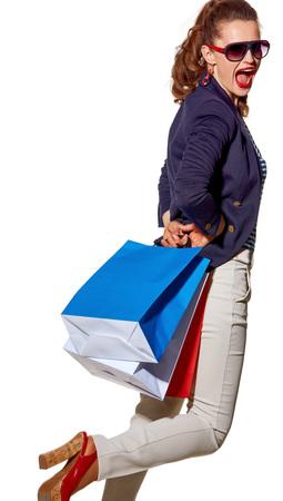 Luxe winkelen. De Franse manier. Volledig lengteportret van vrolijke jonge vrouw met het winkelen zakken in zonnebril die prettijd op wit hebben