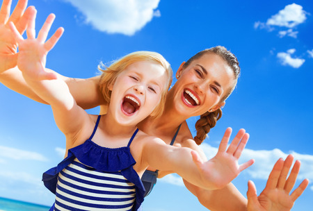 Sun kissed beauty. Portrait of cheerful young mother and child in swimsuit on the seashore having fun time