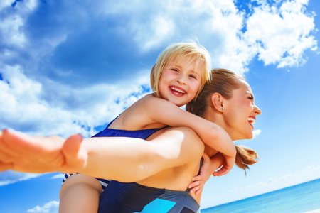 Sun kissed beauty. cheerful healthy mother and child in beachwear on the seacoast having fun time