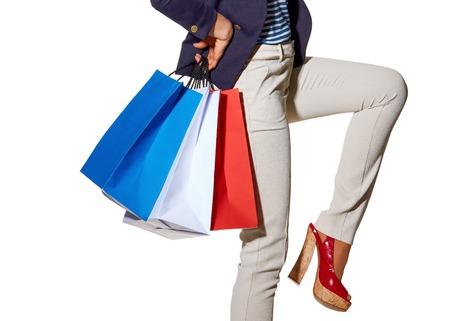 Luxe winkelen. De Franse manier. Close-up op vrolijke jonge vrouw met boodschappentassen in zonnebril poseren op witte achtergrond Stockfoto