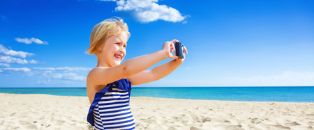 Sun kissed beauty. happy blond child in swimwear on the seacoast with digital camera taking photo Stock Photo