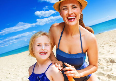 Sun kissed beauty. happy healthy mother and child in swimwear on the seashore applying suntan lotion Foto de archivo - 93807957