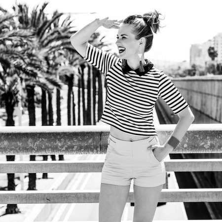 Nosing around, having fun. Full length portrait of happy elegant fashion-monger in yellow shorts and stripy shirt in Barcelona, Spain looking into the distance