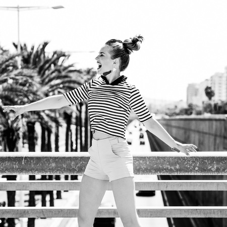 Nosing around, having fun. Full length portrait of cheerful stylish fashion-monger in yellow shorts and stripy shirt outdoors in the city jumping