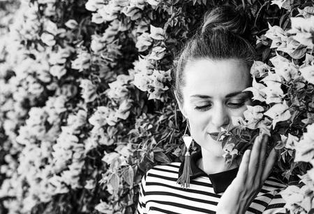 Colorful Freshness. smiling trendy woman in stripy shirt enjoying colorful magenta flowers Stock Photo