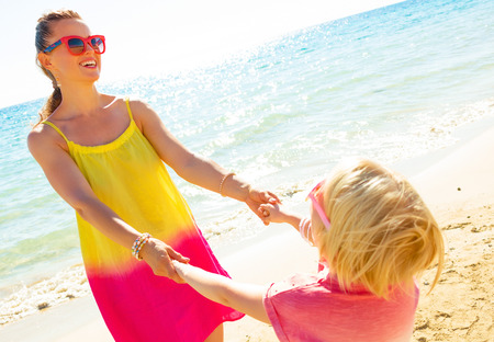 Colorful and wonderfully cheerful mood. smiling modern mother and daughter in colorful clothes on the seacoast having fun time Stock Photo
