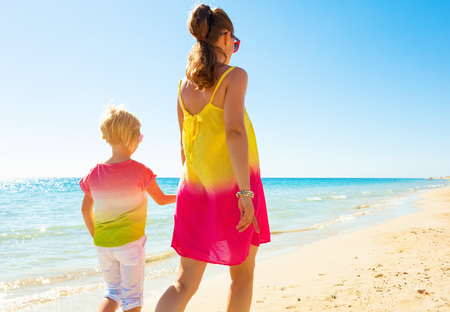 Colorful and wonderfully cheerful mood. Seen from behind trendy mother and child in colorful clothes on the seacoast walking