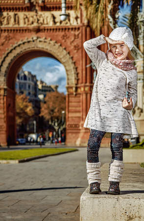 in Barcelona for a perfect winter. Full length portrait of happy trendy girl near Arc de Triomf in Barcelona, Spain looking into the distance