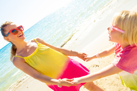 Colorful and wonderfully cheerful mood. smiling modern mother and child in colorful clothes on the seashore having fun time