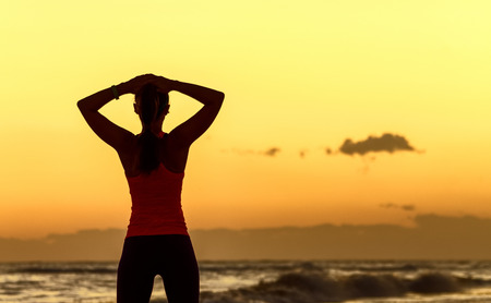 Refreshing wild sea side workout. Silhouette. Full length portrait of relaxed young woman in sports gear standing on the seacoast