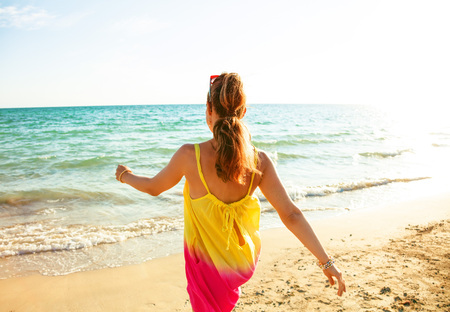 Colorful and wonderfully cheerful mood. Seen from behind young woman in colorful dress on the beach in the evening walking Stock Photo