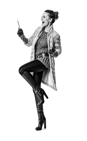 Winter things. Full length portrait of smiling trendy woman in winter coat isolated on white with tablet PC rejoicing