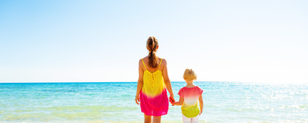 Colorful and wonderfully cheerful mood. Seen from behind trendy mother and daughter in colorful clothes on the beach looking into the distance Stock Photo