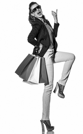 Luxury Shopping. The French way. Full length portrait of cheerful young woman with shopping bags in sunglasses posing on white background Stockfoto