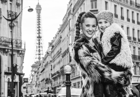 Boiling hot trendy winter in Paris. Portrait of smiling modern mother and child nearby Eiffel tower in Paris, France