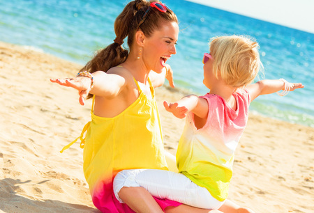 Colorful and wonderfully cheerful mood. smiling modern mother and daughter in colorful clothes on the seashore having fun time