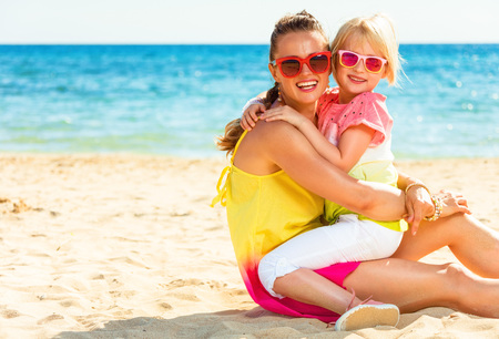 Colorful and wonderfully cheerful mood. Portrait of happy modern mother and child in colorful clothes sitting on the beach Banco de Imagens