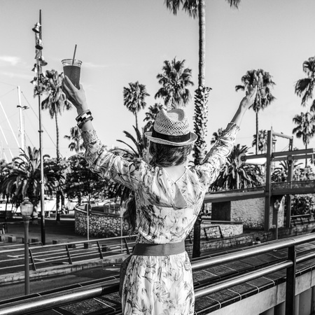 Summertime at colorful Barcelona. Seen from behind stylish tourist woman in long dress and straw hat on embankment in Barcelona, Spain with bright red beverage rejoicing