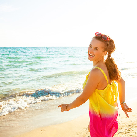 Colorful and wonderfully cheerful mood. smiling young woman in colorful dress on the beach in the evening walking Stock Photo
