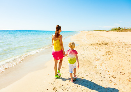 Colorful and wonderfully cheerful mood. Seen from behind modern mother and child in colorful clothes on the beach walking