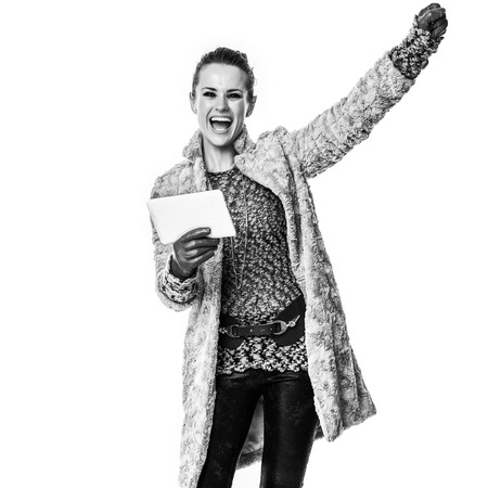 Winter things. Full length portrait of happy modern fashion-monger in winter coat isolated on white with tablet PC rejoicing