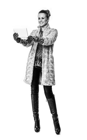 Winter things. Full length portrait of smiling trendy fashion-monger in winter coat isolated on white using tablet PC