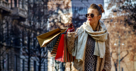 Rediscovering things everybody love in Milan. Full length portrait of young traveller woman with shopping bags in Milan, Italy looking into the distance