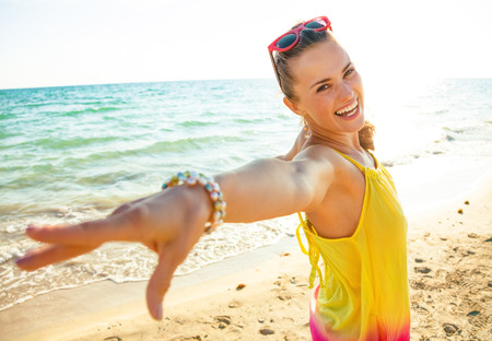 Colorful and wonderfully cheerful mood. Portrait of cheerful trendy woman in colorful dress on the beach in the evening
