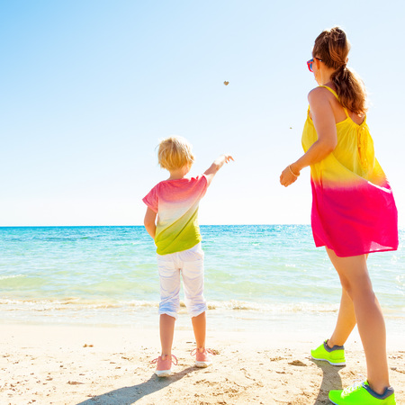 Colorful and wonderfully cheerful mood. Seen from behind trendy mother and daughter in colorful clothes on the seashore throwing stones