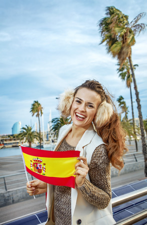 in Barcelona for a perfect winter. smiling young traveller woman in earmuffs in Barcelona, Spain showing flag