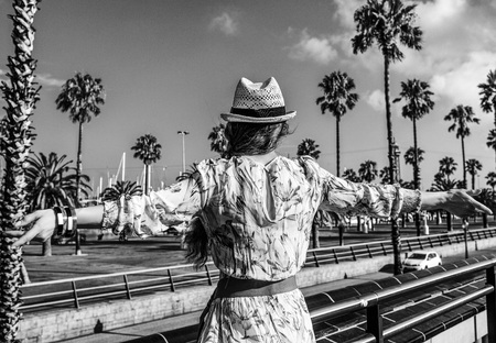 Summertime at colorful Barcelona. Seen from behind elegant tourist woman in long dress and straw hat on embankment in Barcelona, Spain rejoicing