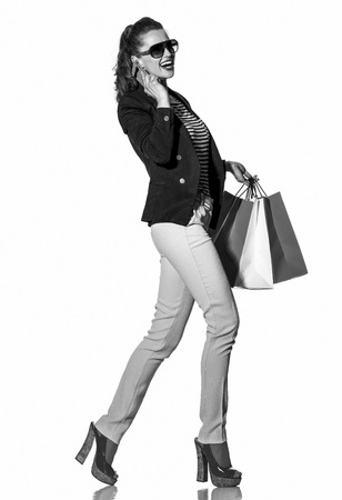 Luxury Shopping. The French way. Full length portrait of happy young woman with shopping bags in sunglasses speaking on a mobile phone and walking isolated on white Stock Photo