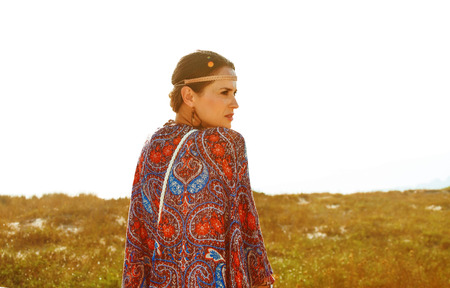 Bohemian vibe vacation. Seen from behind modern gypsy style girl in jeans shorts and cape outdoors in the summer evening looking into the distance