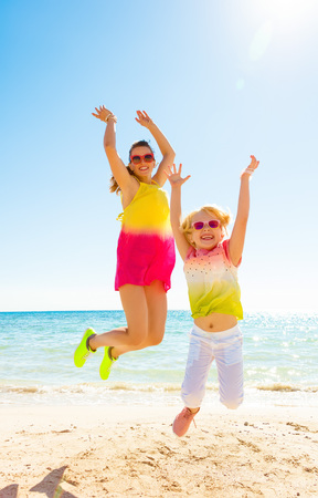 Colorful and wonderfully cheerful mood. Full length portrait of happy trendy mother and child in colorful clothes on the seacoast jumping