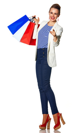 Luxury Shopping. The French way. Full length portrait of smiling modern fashion-monger in white jacket isolated on white background with shopping bags painted in the color of the French flag pointing in camera Stock Photo