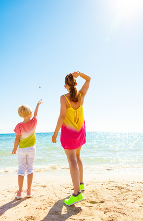 Colorful and wonderfully cheerful mood. Seen from behind modern mother and child in colorful clothes on the beach throwing stones