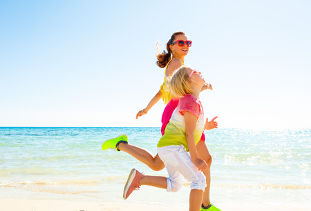 Colorful and wonderfully cheerful mood. smiling modern mother and child in colorful clothes on the seacoast running Stock Photo
